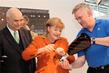 Handarbeit: Otto Kentzler, Pr�sident des ZDH, Bundeskanzlerin Angela Merkel und Klaus-J�rgen Lotz, Pr�sident des BIV f�r Orthop�die-Technik.