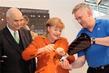 Handarbeit: Otto Kentzler, Präsident des ZDH, Bundeskanzlerin Angela Merkel und Klaus-Jürgen Lotz, Präsident des BIV für Orthopädie-Technik.